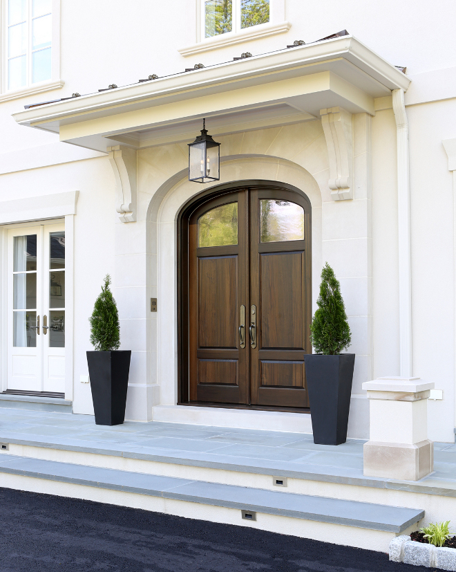 Front Door. The front door features a limestone surround with a wrought iron hanging lantern. The custom curved top paneled mahogany door has antique glass. Standing seam copper roof and bluestone terrace complete the entry. #FrontDoor Knight Architects LLC