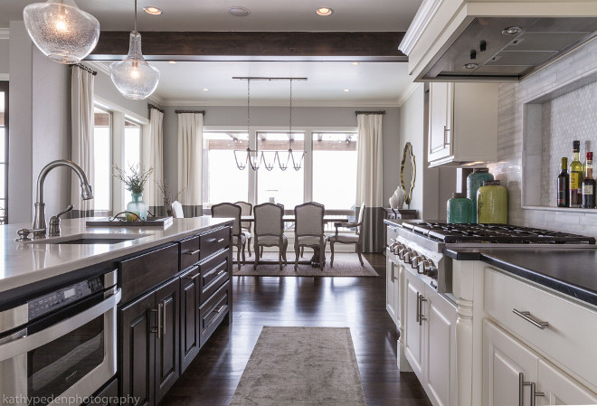 Kitchen with dark stained island. Island is stained in a dark finish with a white quartz countertop. Glass pendants by Kichler Lighting. Kitchen island. Kitchen with dark stained island. #Kitchen #darkstainedisland Restyle Design, LLC.