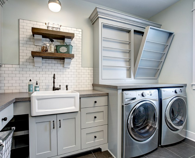 Laundry Room. Farmhouse Laundry Room. Fixer Upper Farmhouse Laundry Room with custom drying rack, subway tile backsplash, open shelves and farmhouse sink. Laundry Room #FarmhouseLaundryRoom #FixerUpperlaundryroom #Farmhouse #LaundryRoom #dryingrack #laundryroomsubwaytile #laundryroom #subwaytilebacksplash #laundryroomshelves #farmhousesink #fixerupper CVI Design