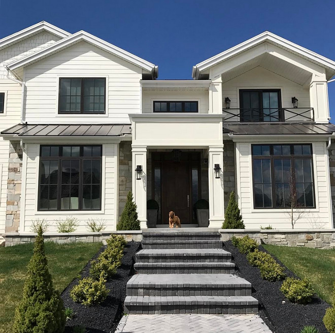 Modern Farmhouse Style Exterior. Modern Farmhouse Style Exterior with white siding, neutral natural stone, Black Paned Windows, custom railing and metal roof. #ModernFarmhouse #ModernFarmhouseStyle #ModernFarmhouseStyleExterior #ModernFarmhouseExterior #FarmhouseExterior #whitesiding #naturalstone #stoneexterior #BlackPanedWindows #railing #metalroof Caitilin Creer Interiors