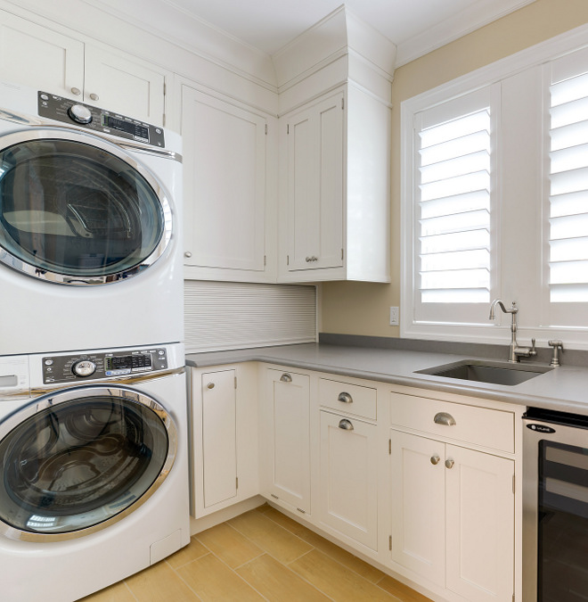 Recessed-panel laundry room cabinet. Recessed-panel cabinetry, quartz countertop and stacked washer and dryer makes the most of this space. Recessed-panel laundry room cabinet and grey quartz countertop #Recessedpanellaundryroomcabinet #Recessedpanelcabinet #laundryroom Echelon Custom Homes