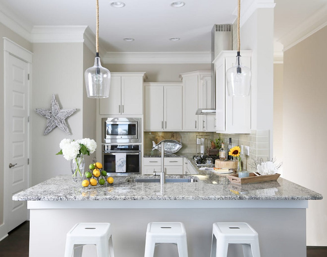 Small Kitchen Inspiration. The cabinets are wood and the designer painted them just a slightly warm white; Sherwin Williams SW 6385 Dover White. The backsplash is glass subway. Subway, to keep it casual but glass for the sparkle! Small White Kitchen with grey backsplash tile, white granite countertop and affordable lighting #SmallKitchen #SmallKitchens #SmallKitchenInspiration #KitchenInspiration #SmallWhiteKitchen #greybacksplashtile #whitegranite #countertop #affordablelighting #lighting JoAnn Regina Home