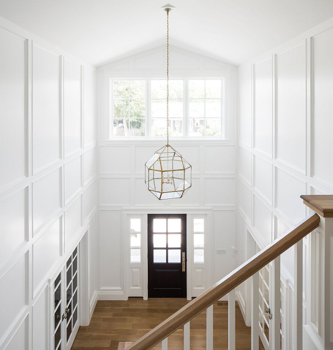 White foyer paneling painted in Simply White by Benjamin Moore. Black door. Lighting is Suzanne Kasler Morris Lantern in Gilded Iron with Clear Glass. White foyer paneling painted in Simply White by Benjamin Moore and Black door #Whitefoyer #foyerpaneling #SimplyWhitebyBenjaminMoore #Blackdoor #Lighting #SuzanneKasler #MorrisLantern #GildedIron #MorrisLanternClearGlass #MorrisLantern Fox Group Construction