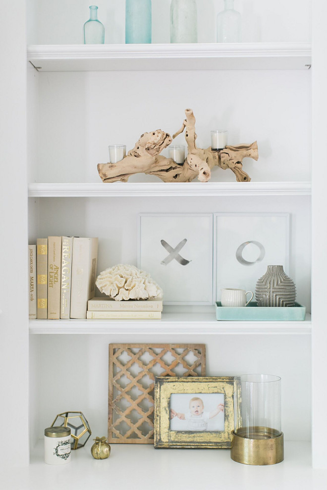 Coastal Bookshelf Decor. Coastal Neutral Bookshelf Decor. Driftwood, photo frames, vintage bottles, linen covered books and a touch of brass accessories. Shelves paint color is Benjamin Moore Decorator's White. Coastal Bookshelf Decor. Coastal Neutral Bookshelf Decor #Coastal #BookshelfDecor #BookshelfDecor #NeutralBookshelfDecor #neutralBookshelf #Bookshelf #Decor Home Bunch Beautiful Homes of Instagram @finding__lovely