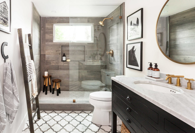Farmhouse Bathroom. Farmhouse bathroom featuring off-white walls, marble flooring, wood-like shower tile and rustic black vanity. #Farmhousebathroom #farmhouse #bathroom #tile #woodliketile #rusticvanity #offwhite Juxtaposed Interiors