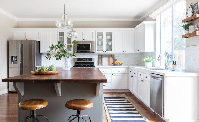 Fixer Upper Farmhouse Kitchen Reno Tips and Ideas. The original cabinet doors were taken off and replaced with new shaker style cabinet faces. The original frame of the cabinets remained, but was sanded down, sealed and painted to remove any signs of grain. Fixer Upper Farmhouse Kitchen Reno Tips and Ideas #FixerUpper #FarmhouseKitchen #FixerUpperKitchen #RenoReno #RenoTips #Kitchenrenoideas #fixerupperreno #fixerupperIdeas Juxtaposed Interiors