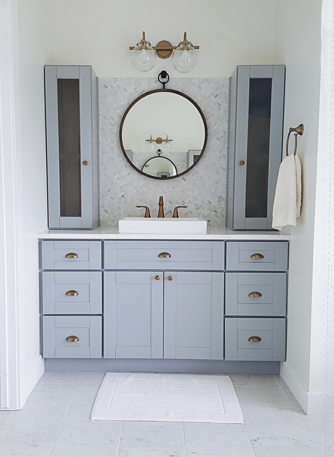 Grey Bathroom Cabinet. I didn't want to spend a lot. I really wanted to achieve a designer look on a budget. We were able to get the look we wanted on our budget this in several different ways. First, I went with RTA cabinets (ready to assemble) this saved us A LOT of money. RTA cabinets are usually about half the cost of custom cabinets and you can get several different finishes, styles and options to go with your design and budget. Grey Bathroom with grey cabinets, brass hardware, brass lighting and herringbone backsplash tile #GreyBathroom #GreyBathroomCabinet #Bathroom #grey cabinets #brasshardware #brasslighting #herringbonebacksplash #herringbonebacksplashtile #backsplashtile Home Bunch's Beautiful Homes of Instagram @household no.6