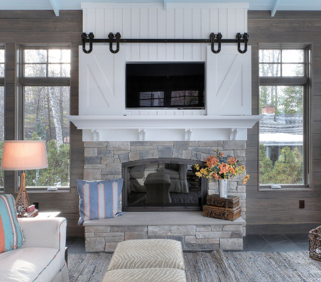 Sliding Barn Door TV Cover. This farmhouse-style fireplace features a sliding barn door TV cover. Farmhouse Sliding Barn Door TV Cover. Fireplace Sliding Barn Door TV Cover. #SlidingBarnDoorTVCover #FarmhouseSlidingBarnDoorTVCover #FireplaceSlidingTVBarnDoor #TVCover MAC Custom Homes