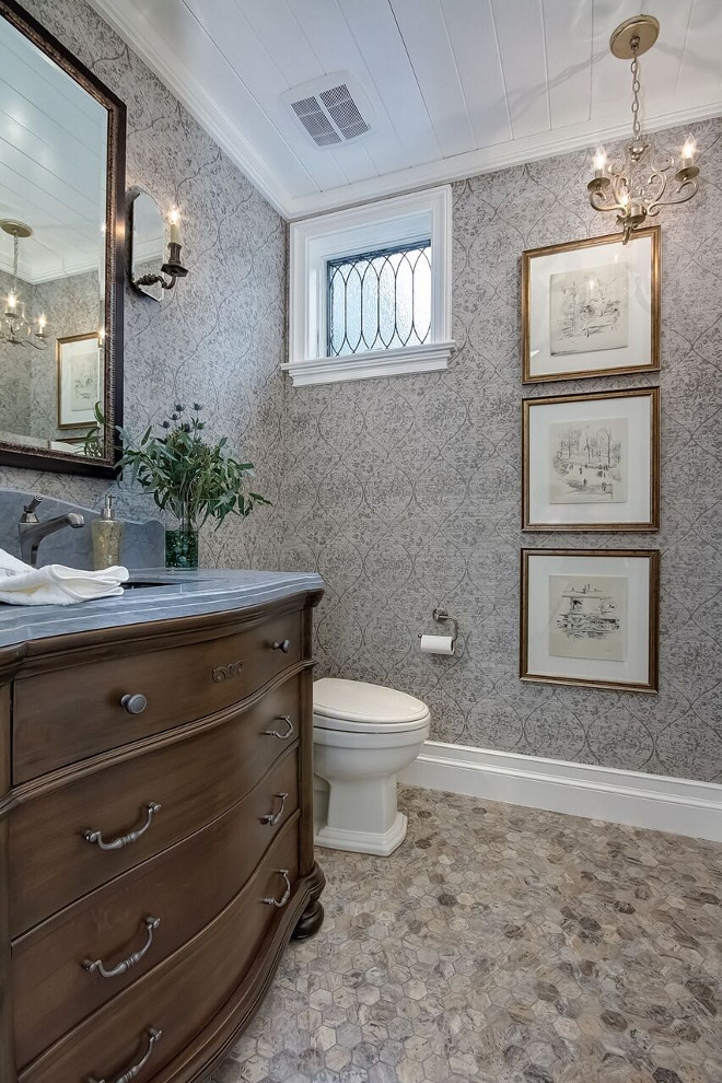 This traditional powder room features a dresser-style vanity and a grey and beige hex marble floor tile. #hextile #powderroom #bathroom Brandon Architects, Inc.