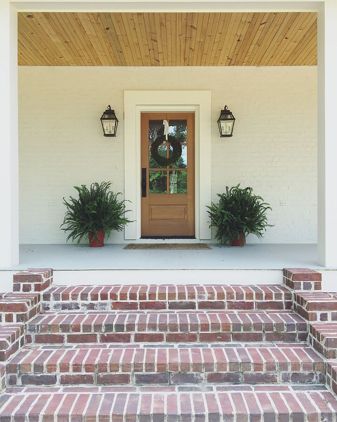 Farmhouse brick porch steps. Farmhouse brick porch step ideas. To bring in that Southern coastal feel, we had lanterns with the look of gas burning, and we used expose brick piers under the porches and tied them together with cream painted wood slats. Front Door: Simpson #7506 Thermal Sash Fir.  Stain: Sherwin Williams Woodscapes in Covered Bridge.  Door Trim: Emtek 451613 Rectangular Full Length Tubular Entrance Handleset with winchester interior knob - in flat black.  Farmhouse brick porch steps. Farmhouse brick porch steps #Farmhouse #brickporchsteps #bricksteps #porchsteps Beautiful Homes of Instagram @theclevergoose