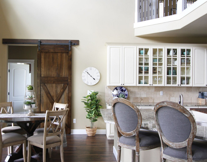 Farmhouse kitchen with creamy white cabinets, light tan walls and barn door. Home Bunch's Beautiful Homes of Instagram @AshleysDecorSpace_