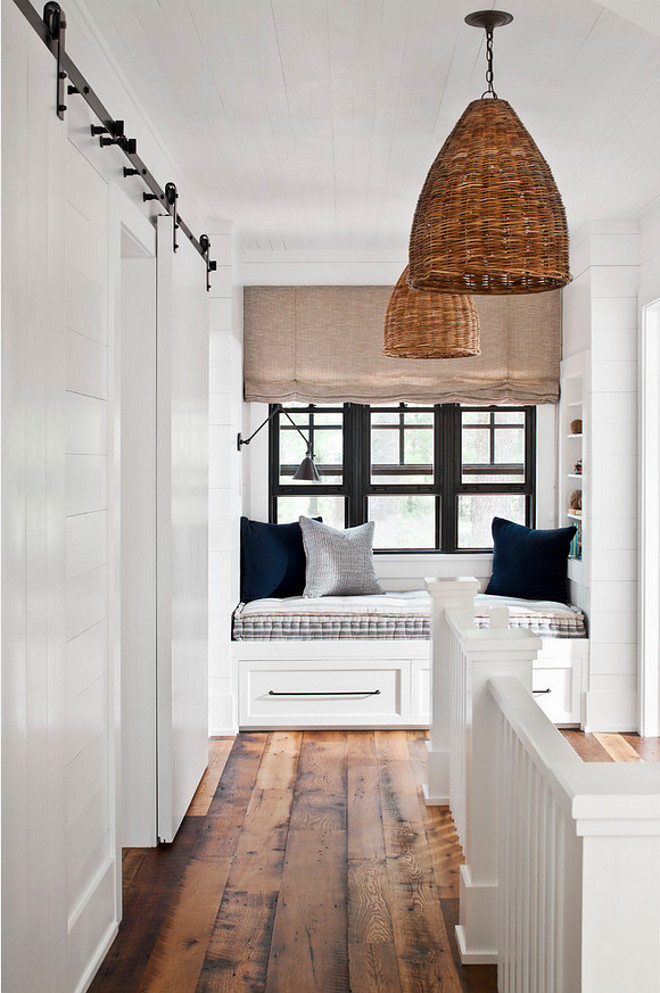 Farmhouse landing with shiplap, window seat reading nook, barn door, basket pendants and rustic wide plank hardwood floor. Farmhouse landing with shiplap, window seat reading nook, barn door and rustic wide plank hardwood floor #Farmhouse #farmhouselanding #shiplap #windowseat #readingnook #barndoor #rusticwide #plankhardwoodfloor #basketpendants Jennifer Worts Design Inc