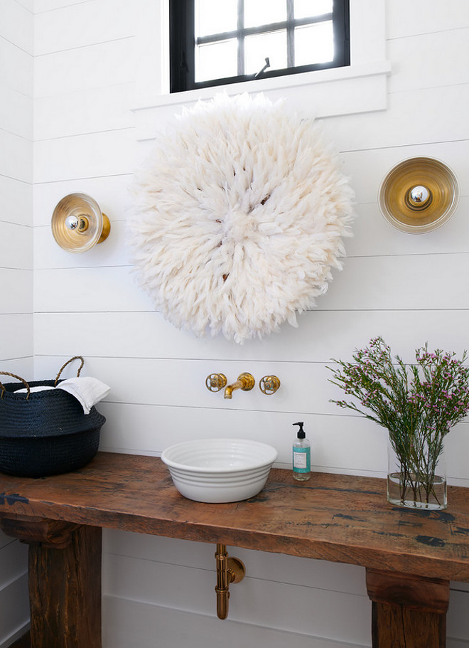Farmhouse powder room boasts a shiplap wall lined with a white juju hat while gold sconces are placed over a repurposed console table topped with a white bowl sink and an antique brass faucet mounted on the wall. #farmhouse #powderroom #farmhousepowderroom #farmhousebathroom #bathroom Jennifer Worts Design Inc