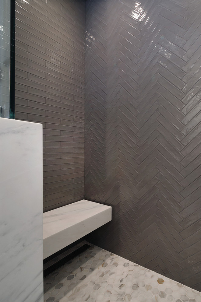 "Shower with marble hexagon pieces, and floating shower seat covered in an honed pacific white marble slab. This shower brings quite the design impact with its back wall featuring Italian-made Piastrell Grigio set in a herringbone pattern, floor tiled with 2"" marble hexagon pieces, and floating shower seat covered in an honed pacific white marble slab. This shower also features 2"" marble hexagon floor tile and a floating shower seat covered in an honed Pacific White Marble slab. Patterson Custom Homes"