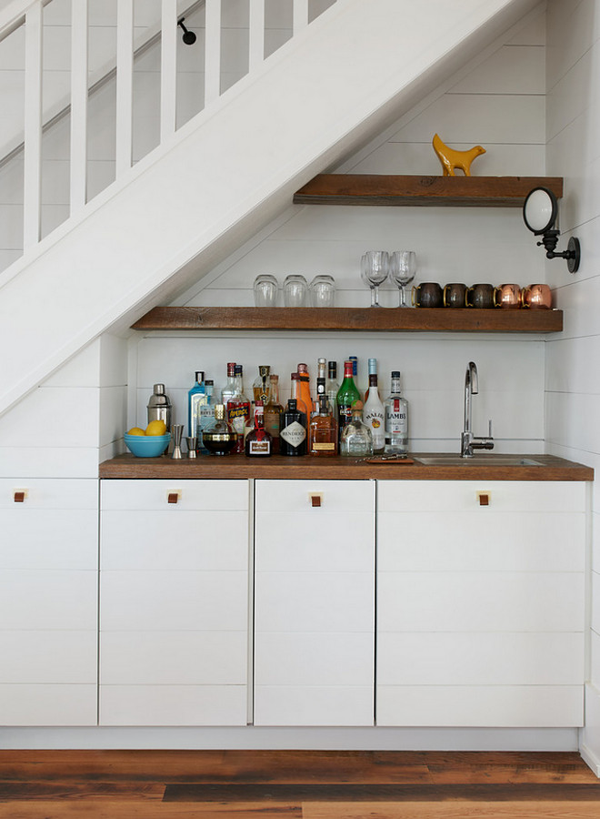 Wet Bar under stairs. Wet Bar under staircase. Built in wet bar under the stairs with floating shelves and shiplap cabinets and shiplap paneling. Wet Bar under the stairs #WetBarunderstairs #WetBar #Barunderstaircase Jennifer Worts Design Inc