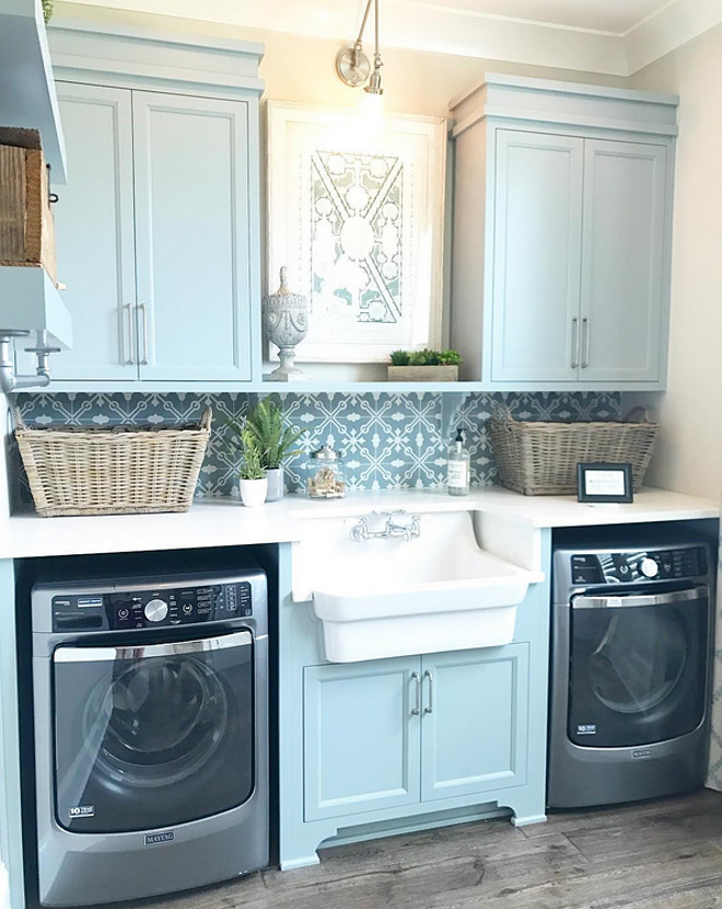 Laundry room with sink. Laundry room sink. Laundry room features Blue gray cabinets and a farmhouse sink flanked by a pair of gray washer and dryer. Countertop is white quartz and backsplash is patterned cement tile. #laundryroom #bluegraycabinets #laundryrooms #cementtile #patternedtile #quartzcountertop #sink #farmhousesink #laundryroomsink Artisan Signature Homes