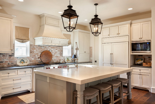 Traditional Cream White Kitchen with light glazed cabinets, warm grey island and exposed brick backsplash #traditionalkitchen #creamwhitekitchen #creamwhitekitchencabinets #glazedcabinet #lightlyglazedcabinets #exposedbrick #exposedbrickbacksplash #brickbacksplash Frankel Building Group