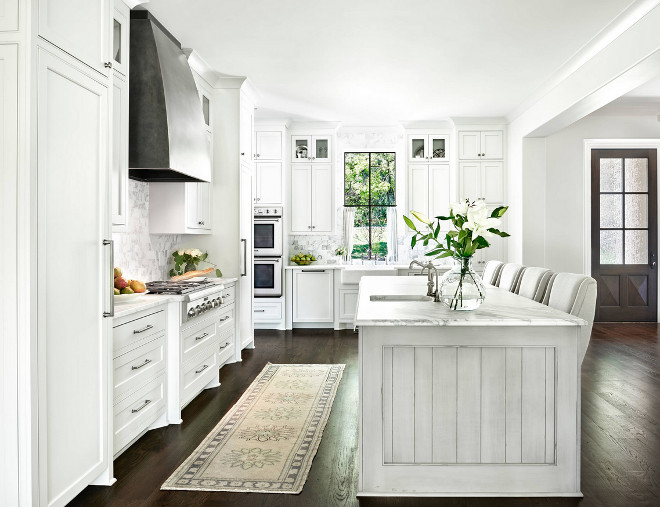 White kitchen with dark hardwood floors, zinc hood, Bianco carrara backsplash tile and black steel window. White kitchen with dark hardwood floors, zinc hood and black steel window ideas. Countertops are honed Calacatta Gold marble with an cove ogee edge. White kitchen with dark hardwood floors, zinc hood and black steel window #Whitekitchen #darkhardwoodfloors #zinchood #blacksteelwindow Forte Building Group LLC