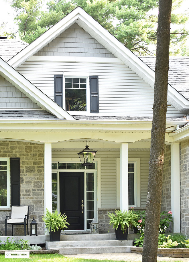 The black front door paint color is Canadian Tire Premier Exterior Paint - Midnight, Semi-gloss. What a timeless paint color #homeexterior #greystone #siding #blackdoor #pendant Beautiful Homes of Instagram @citrineliving Home Bunch