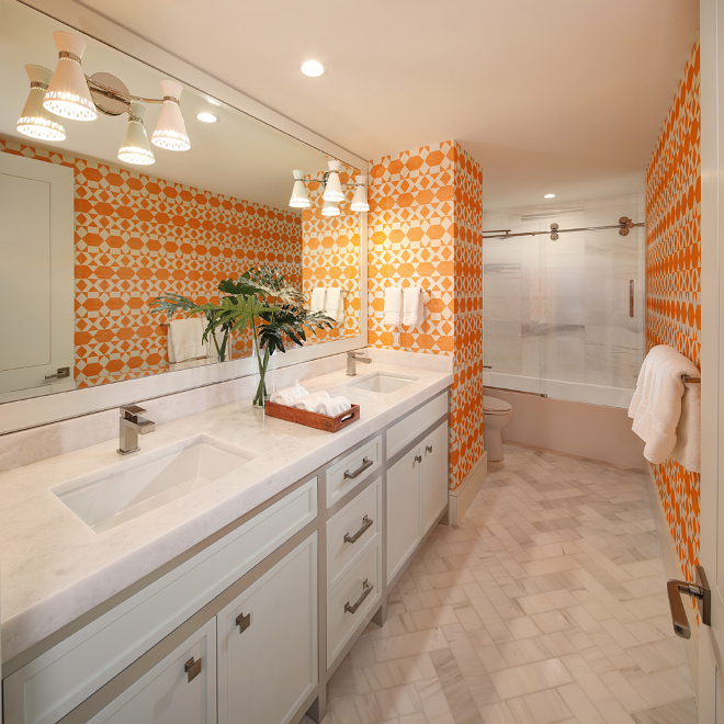 Bathroom. Bold, bright and full of personality, this powder room is adorned in Phillip Jeffries Nomadic wallcovering. The floor tile is a gorgeous Dolomite marble laid in a herringbone pattern. Sconces are Jonathan Adler Havana Sconce. W Design