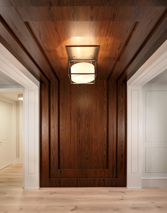 Entry wall paneling. The entry features a modern twist on wall paneling by creating a flush panel detail with a recessed groove. The rosewood feature wall seamless runs up the wall and across the ceiling. Trim/Ceiling Paint: Benjamin Moore OC-17 White Dove. #rosewood #paneling #wallpaneling #entry #foyer W Design
