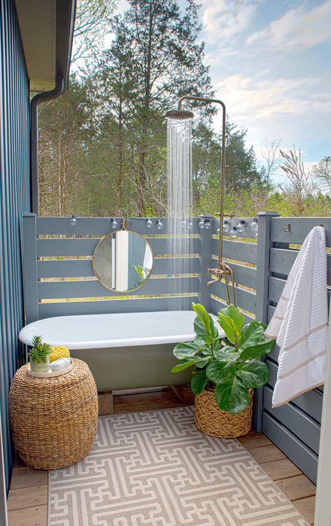 Outdoor Shower Fence. The Outdoor Shower Fence is pressure-treated 1x4's painted with exterior paint. The designer's husband built it and it's parallel style fence. The blue was color match to the color of our board and batten siding. #outdoorshowerfence #outdooorshowerfence #parallelstylefence Sharon Barrett Interiors