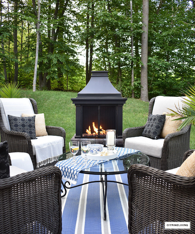 outdoor-fireplace-lounge-area-whicker-wingback-chair-blue-and-white-striped-rug Beautiful Homes of Instagram @citrineliving Home Bunch