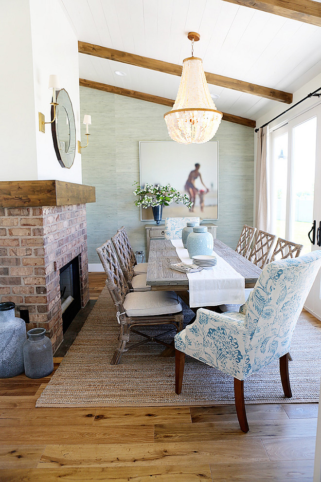 Coastal Dining room with grasscloth wallpaper, brick fireplace and glass chandelier Millhaven Homes. Caitlin Creer Interiors