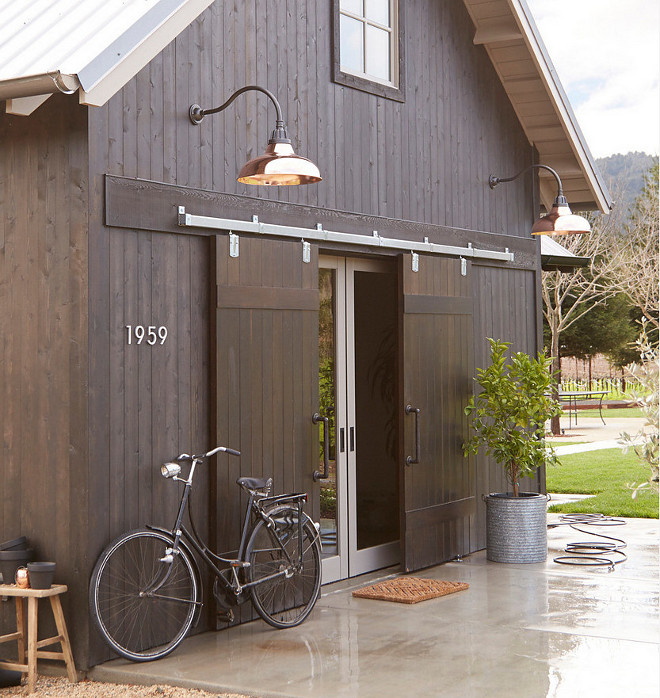 Copper Barn lights. Barn style home with exterior barn doors and copper barn lights. Lighting is Rejuvenation Carson Gooseneck #barnlights #copperbarnlight #barnlighting #exterior #barnlighting #lighting Photo By Rejuvenation