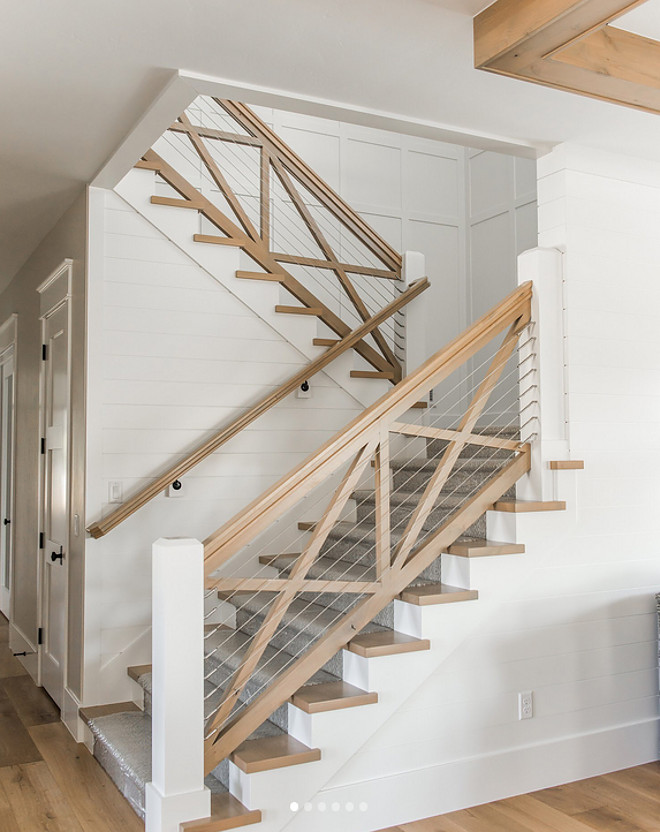 Farmhouse Staircase. Farmhouse staircase features white oak railing and white oak crossed wood balusters and cable railing. Farmhouse staircase features white oak railing and white oak crossed wood balusters and cable railing. Walls feature a combination of shiplap and board and batten grid paneling #Farmhousestaircase #whiteoakstaircase #railing #whiteoakrailing #crossedwoodbalusters #cablerailing #shiplap #boardandbattengrid #paneling Millhaven Homes
