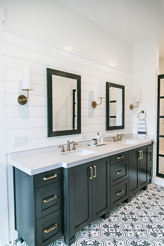 Farmhouse Bathroom. Farmhouse bathroom with black cabinet, shiplap behind vanity, black framed mirrors, black framed shower doors, black and white patterned tiles, brass hardware and lighting and white quartz countertop. #farmhouse #bathroom #farmhousebathroom #shiplap #patternedtiles #patternedtile #brasshardware #blackandwhite #bathrooms #tile #farmhouse #whitequartz #countertop Sita Montgomery Interiors