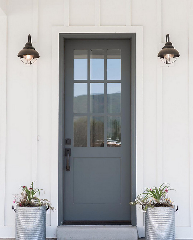 Farmhouse front door with zinc planters. Farmhouse with board and batten siding, grey front door with zinc planters. Farmhouse front door with zinc planters #Farmhouse #frontdoor #zincplanters Millhaven Homes