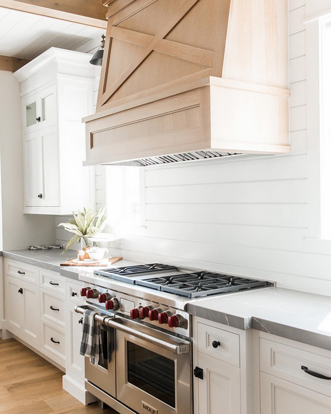 Farmhouse kitchen with white oak hood and shiplap backsplash. Millhaven Homes