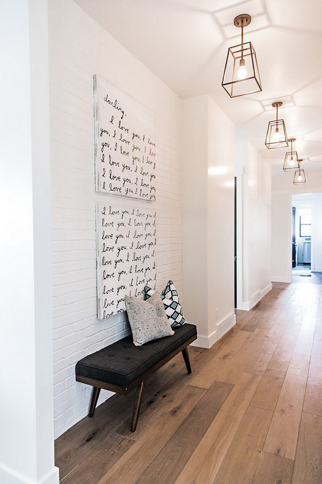 Hardwood Floor and painted brick accent wall. Hall features wide plank white oak hardwood floors, painted brick accent wall and brushed brass lantern lighting. #hardwoodfloor #paintedbrick #brickwall #accentwall Sita Montgomery Interiors