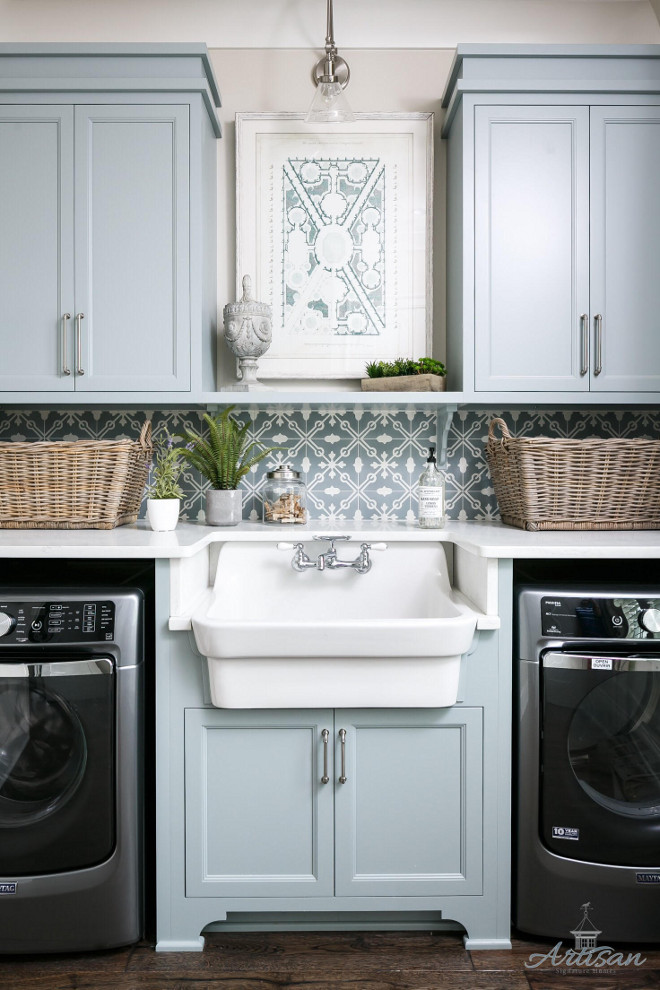Laundry room farmhouse sink. Laundry room farmhouse sink between washer and dryer. Laundry room with grey blue cabinets, painted in Silver Mink by Benjamin Moore, patterned tile backsplash and farmhouse sink #laundryroom #farmhousesink Artisan Signature Homes