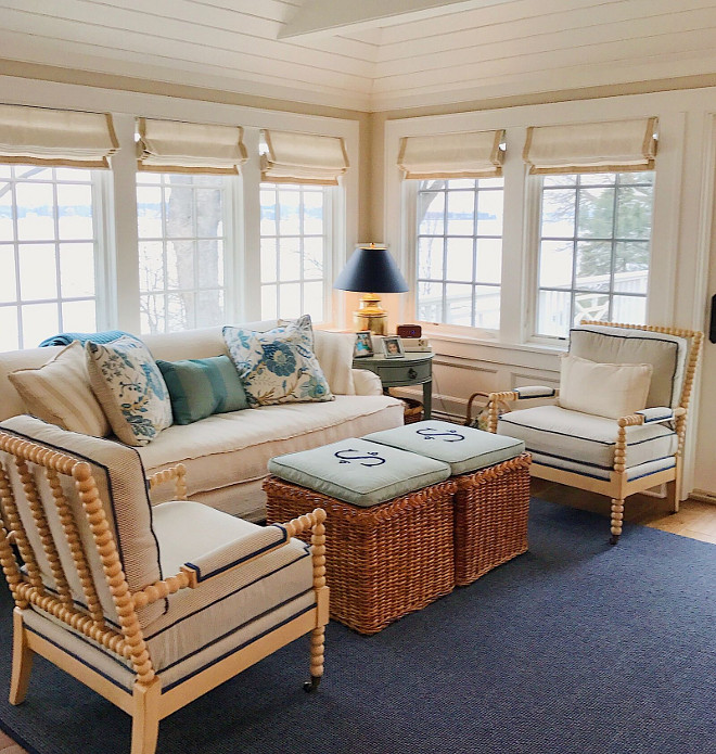 Sitting room. Coastal sitting room with spindle chairs, blue and white pillows, white linen Roman shades, rattan ottomans and navy blue rug. #sittingroom #coastal #coastalinteriors Beautiful Homes of Instagram @SweetShadyLane