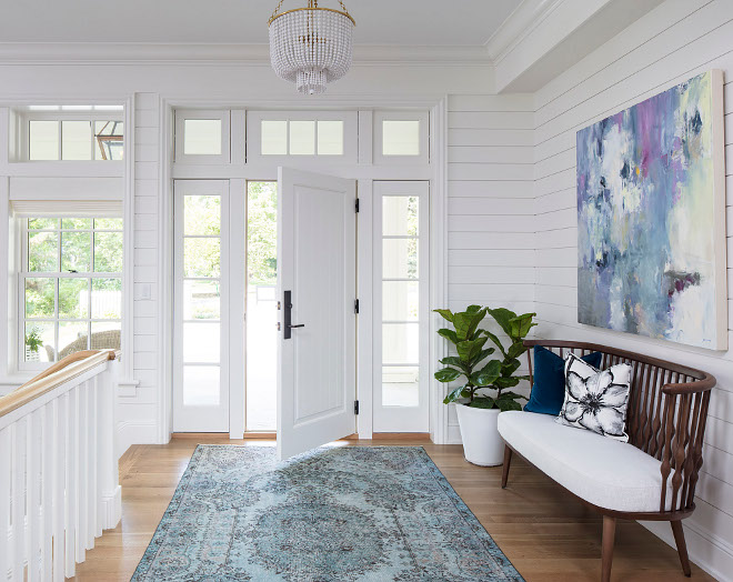 White foyer with white shiplap, white oak hardwood floors and white front door with sidelights. An original art and a blue foyer rug brings some color to this white space. White foyer with white shiplap, white oak hardwood floors and white front door with sidelights. An original art and a blue foyer rug brings some color to this white space. White foyer with white shiplap, white oak hardwood floors and white front door with sidelights. An original art and a blue foyer rug brings some color to this white space #Whitefoyer #whiteshiplap #shiplap #whiteoak #hardwoodfloors #whitefrontdoor Martha O'Hara Interiors