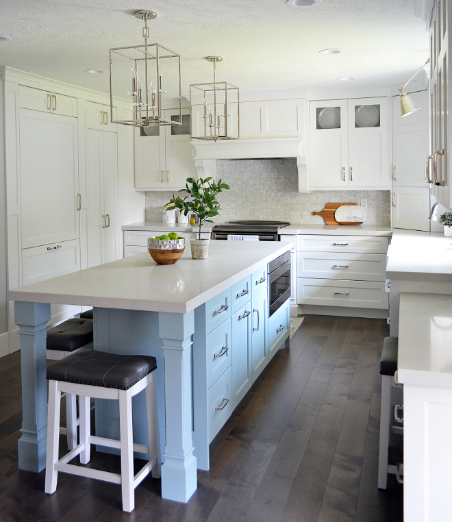 Kitchen with narrow and long island. White kitchen with a long and narrow kitchen island painted in a light turquoise blue color and white quartz countertop. #kitchen #narrowisland #narrowkitchenisland #longkitchenisland #whitequartz #countertop #turquoisekitchenisland Sita Montgomery Interiors