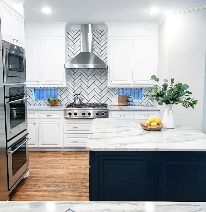 White kitchen with herringbone backsplash with black grout. Cabinet paint color is Benjamin Moore Chantilly Lace. Tile is Daltile Modern Dimensions Glazed Ceramic, 0190 in Arctic White. White kitchen with herringbone backsplash with black grout. White kitchen with herringbone backsplash with black grout. White kitchen with herringbone backsplash with black grout. #Whitekitchen #herringbonebacksplash #blackgrout Lark Interiors