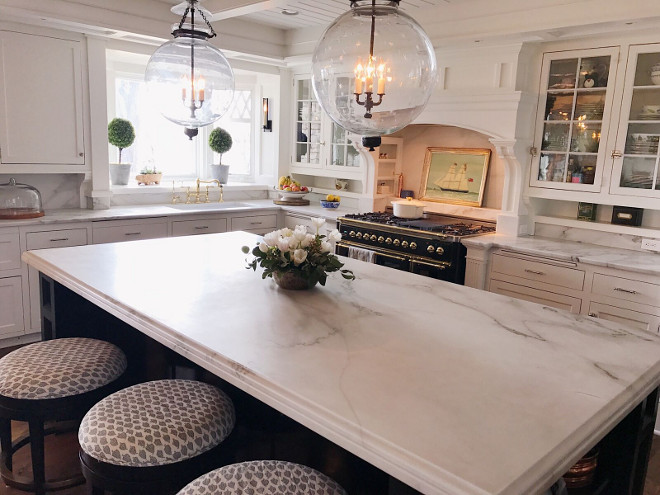 Classic white kitchens. White Carrera marble on countertops and backsplash, Silver hardware on cabinets. Tempered antique glass in upper cabinets. Island measures 106 by 54' and is painted Benjamin Moore black with antique brass pulls. Kitchen faucet is gold and with a farm house sink. I love mixing metals in a kitchen. Black and brass stove is ILVE and I love its form and function. Star pendant lights are antiques from Nantucket. #classickitchens #classicwhitekitchens #kitchen Beautiful Homes of Instagram @SweetShadyLane