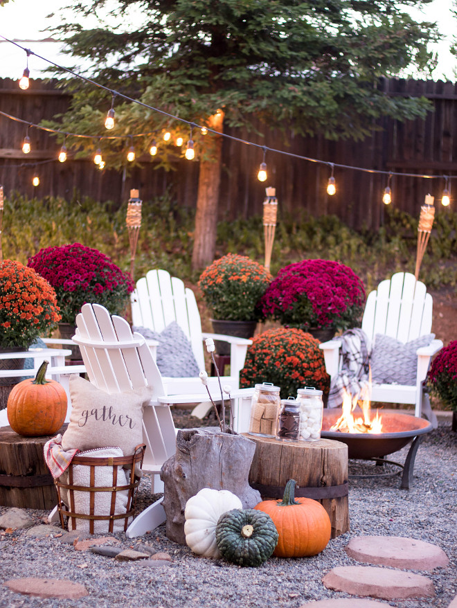 Fall Backyard Decor ideas. Backyard decorated for Fall with many mums, pumpkins, adirondack chairs and outdoor string lights. Fall Backyard @idreamofhomemaking