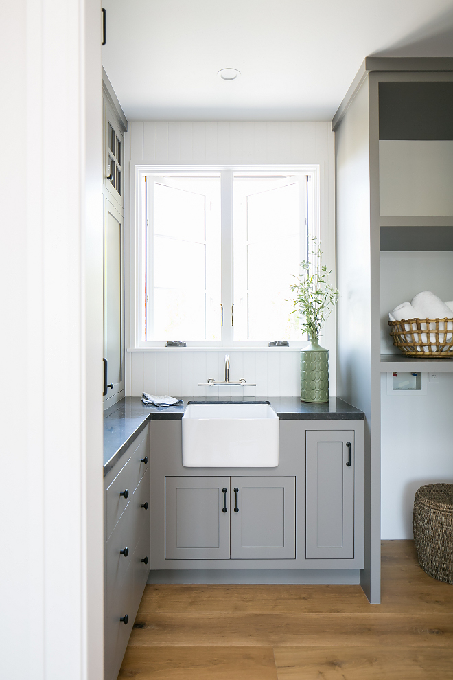 Grey laundry room with small farmhouse sink This grey laundry room features a small farmhouse sink and honed Belgian Limestone countertop