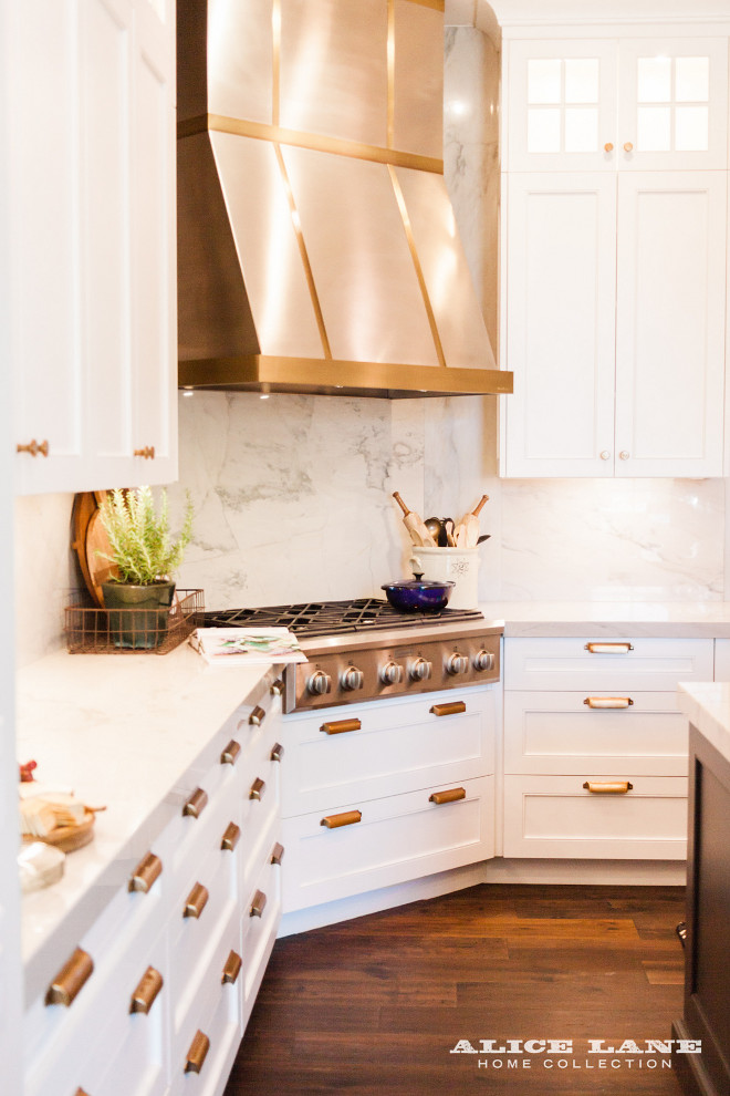 White kitchen with brass hardware, steel hood with brass strip and white quartzite countertop and full slap backsplash Alice Lane Home Collection