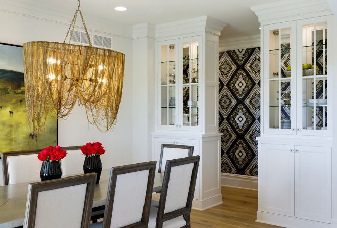 Dining room features a brass chandelier and built in cabinets The dining room features custom designed glass hutches, panel molding accent wall and a chandelier dripping with mixed metal chains