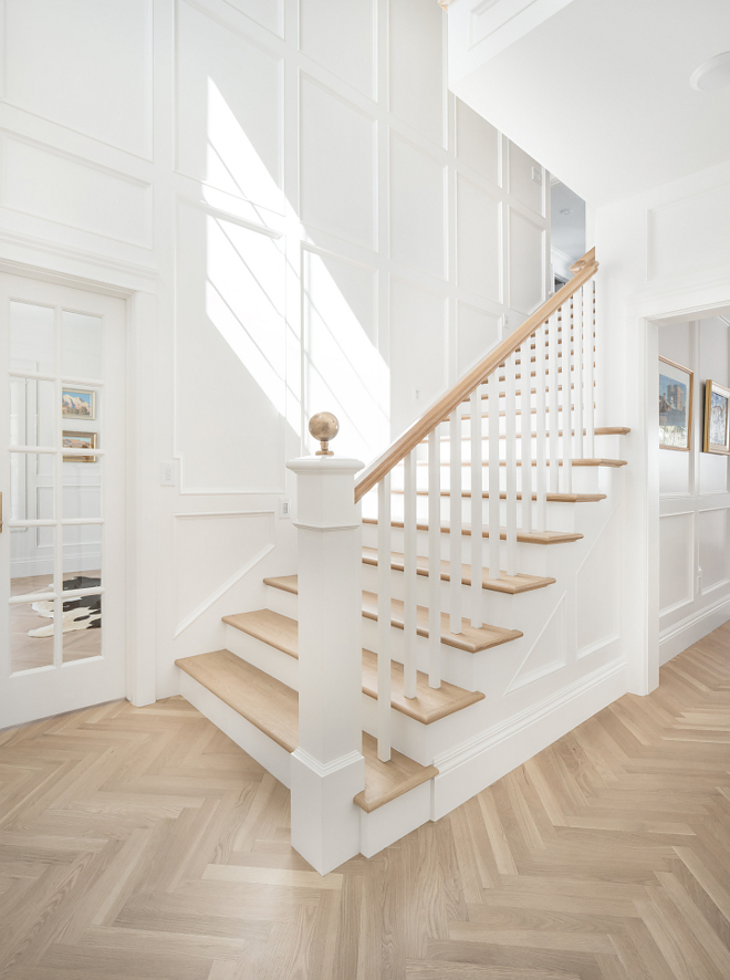 Foyer wall paneling and herringbone hardwood floor Crisp white foyer painted in Benjamin Moore Simply White with classic paneled walls and herringbone hardwood floors #BenjaminMooreSimplywhite #paneling #foyer #herringbonefloors