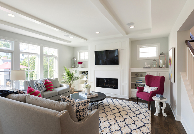 Living room with grey walls and white media cabinet flanking fireplace This living room features grey walls and white media cabinet flanking a fireplace with white paneling