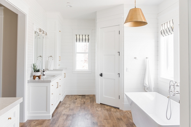 White bathroom with brass lighting and brass hardware