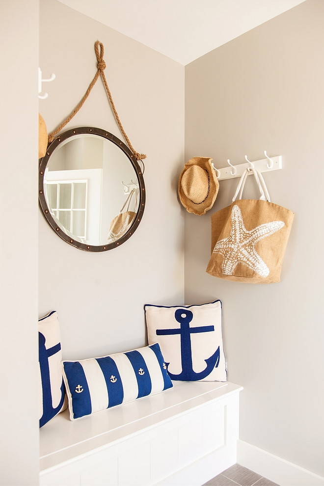 Coastal mudroom painted in Revere Pewter by Benjamin Moore and blue and white anchor pillows and round mirror with rope