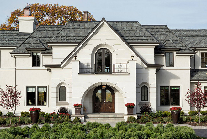 French style home with beige stucco siding and black windows