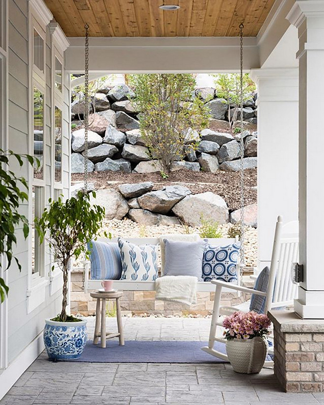 Front porch swing with blue and white pillows